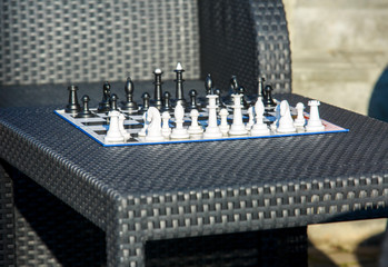 chessboard on the rattan table in the garden in the summer. Travel, vacation, holidays concept  Education concept, chess lesson, training, intellectual game