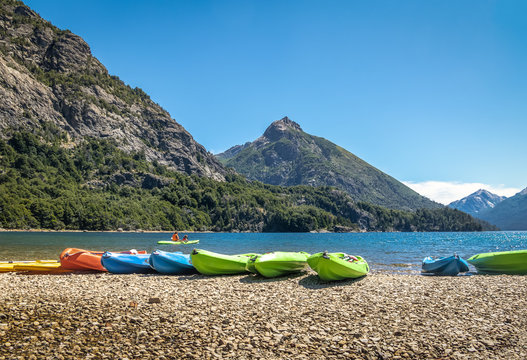 Colorful Kayaks in a lake surrounded by mountains at Bahia Lopez in Circuito Chico  - Bariloche, Patagonia, Argentina
