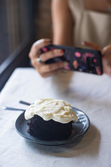 woman taking picture of dark chocolate cake with cream cheese on the table.
