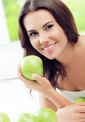 happy smiling woman with green apples, indoors