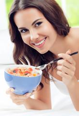 Cheerful beautiful young woman eating muslin