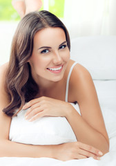 Young beautiful smiling woman waking up, at bedroom