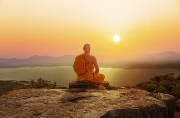 Buddhist monk in meditation at beautiful sunset or sunrise background on high mountain Wall mural