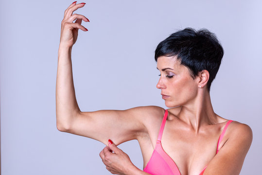 Calm woman stretching skin on bent arm