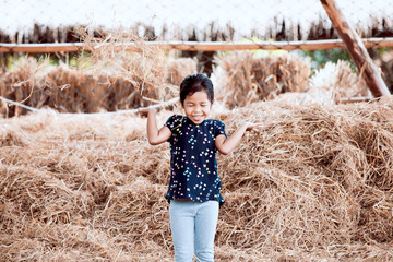 Cute asian child girl having fun to play with hay stack in the farm with happiness