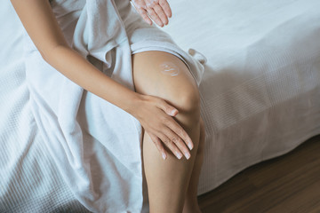 Woman applying moisturizing cream on her legs,Concept healthy and skin