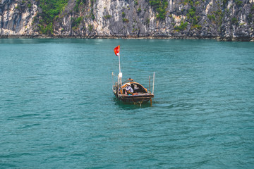 A fishing boat with a Vietnamese flag and a fisherman in the Halong Bay. Vietnam