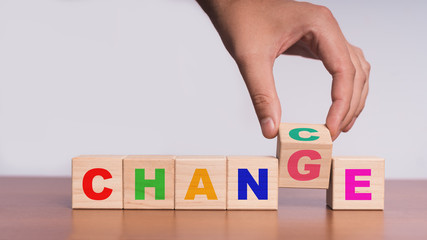 """Hand hold flip wooden cube with word """"change"""" to """"chance"""""""