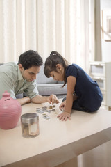 Father and daughter counting piggy bank coins