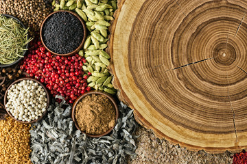 Fototapete - Various spices and herbs background. Condiments with empty wooden surface.