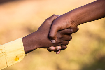 Black boys shaking hands close up