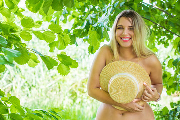 Attractive plus size young lady at nature. Portrait of voluptuous young woman posing sensually on green outdoor background