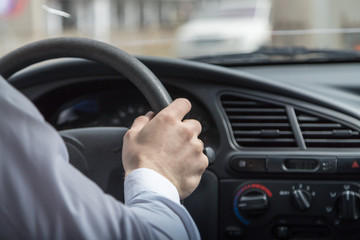 Man hands holding steering wheel while driving car