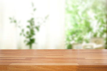 Empty of wood table top on blur of abstract green from garden with sunlight and curtain window , product display