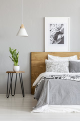 Plant on table next to wooden bed in grey bedroom interior with lamp and poster. Real photo