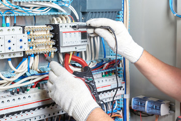Closeup of an electrician's hand with a diagnostic tool in his hand