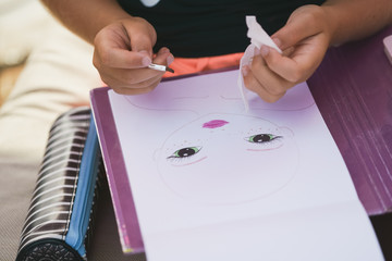 Girl draws in album with brush on beach