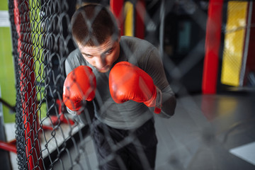 Fotorolgordijn Rood, zwart, wit Male boxer engaged in training in the gym, in a cage for a fight without rules, Boxing coach