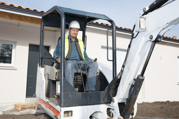 construction man worker operating a track hoe machine