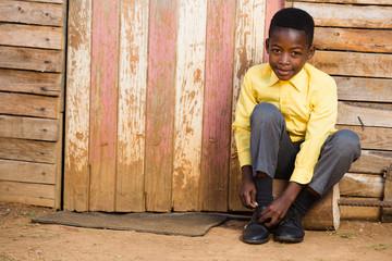 Cute black boy tieing his shoes
