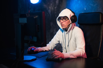 male hooded gamer playing online game on pc computer