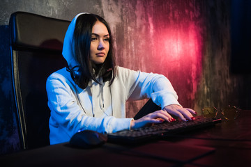 young hooded female hacker developing malware