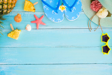 Holidays concept. Pineapple slices, shells, starfish, slippers, straw hat and sunglasses on wood plank blue color. Summer vacation background concept. top view