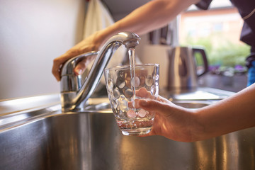 Close up of woman and children hands, pouring glass of fresh water from tap in kitchen