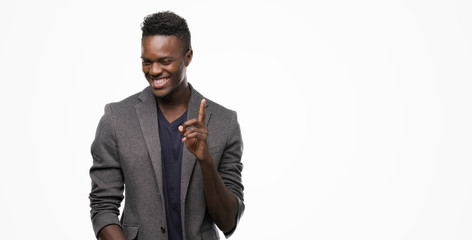 Young african american man wearing a jacket surprised with an idea or question pointing finger with happy face, number one