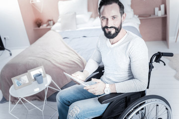 Home atmosphere. Positive differently abled man holding tablet in both hands while working at home