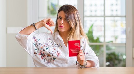 Young woman at home holding a passport of Switzerland with angry face, negative sign showing dislike with thumbs down, rejection concept