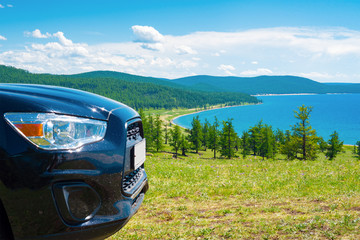 Car travel. The front part of the car on the background of Lake Hovsgol, Mongolia
