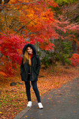 woman smile at the Red maple leaves in garden.