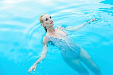 gorgeous young woman in clear blue water of smimming pool