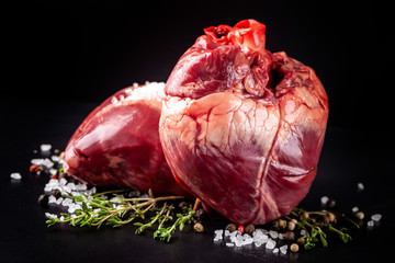 Beef raw heart on a black background with rosemary and spices.