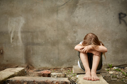 Street photo of girl orphan with holen knees under the dirty city wall.