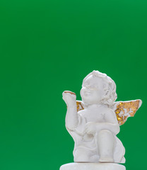 Figurine Of Baby Angel On Green Background