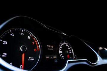Close up shot of a speedometer in a car. Car dashboard. Dashboard details with indication lamps.Car instrument panel. Dashboard with speedometer, tachometer, odometer. Car detailing. Modern interior