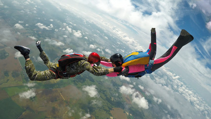 Two skydivers making a formation in the air