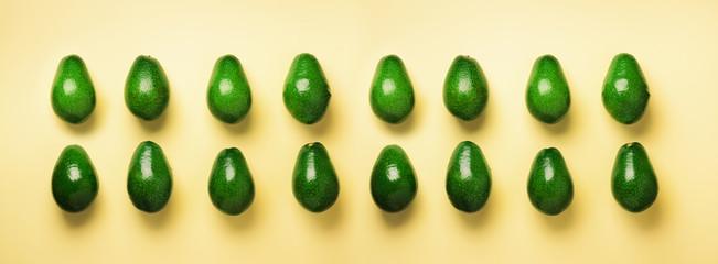 Green avocado pattern on yellow background. Banner. Top view. Pop art design, creative summer food...