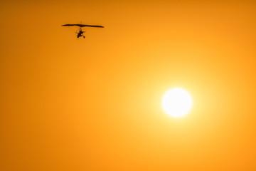 Motor glider flying high in orange sunset sky on sun disc background