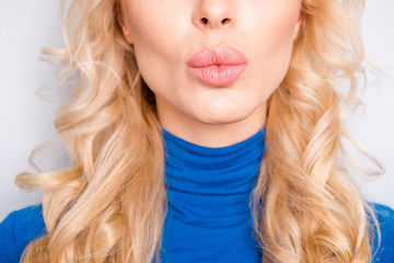 Cropped, close up, half face portrait of pretty, trendy, charming, lovely, nice, sexy, cute, blonde woman in blue roll neck isolated on grey background sending air kiss with pout lips to the camera