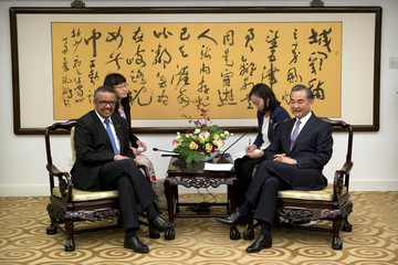 Tedros Adhanom Ghebreyesus, left, Director General of the World Health Organization (WHO), and Chinese Foreign Minister Wang Yi, right, smile as they pose for photos before the start of a meeting at the Ministry of Foreign Affairs in Beijing