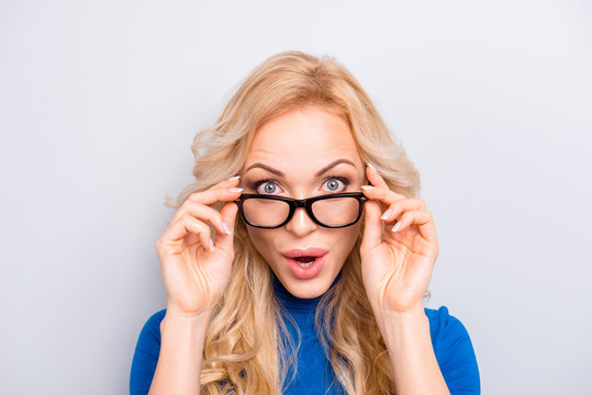 Portrait of pretty, trendy, charming,  nice, sexy, cute, shocked, frustrated woman isolated on grey background looking out glasses with wide open eyes holding eyelet with fingers