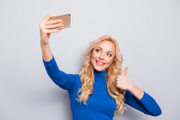 Pretty, trendy, charming, nice, sexy, cute, cheerful woman in blue turtleneck shooting selfie on smart phone in her hand gesturing thumb up with finger having fun, video-call, rest, relax, leisure