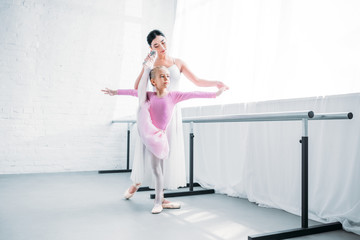adorable little ballerina in pink tutu exercising with teacher in ballet school