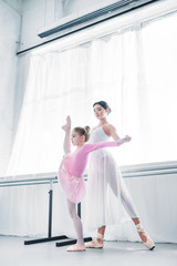 low angle view of young ballet teacher training with child stretching in ballet school