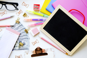 Educations costs. Stack of multiple one hundred dollar bills, planner notebook empty check box, colorful pens, school supplies, blank screen tablet, glasses. Background, flat lay, close up, copy space