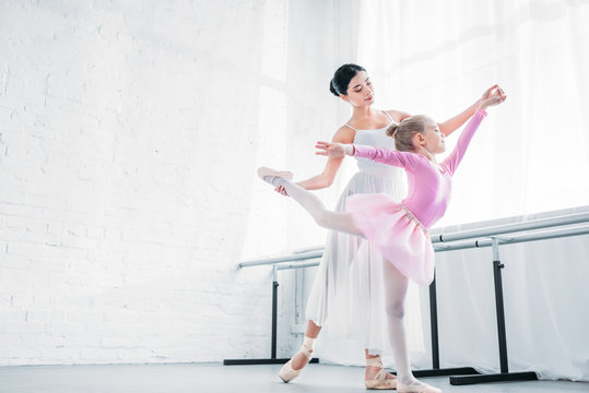 low angle view of adult ballerina training with child in pink tutu in ballet studio