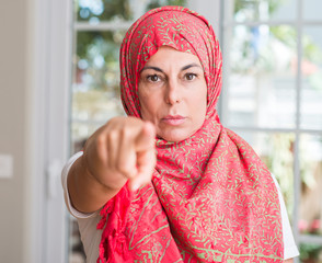 Middle aged muslim woman wearing hijab pointing with finger to the camera and to you, hand sign, positive and confident gesture from the front